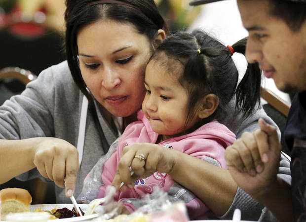 Laura Bobadilla cuts a piece of turkey into small bites for her daughter, Sofia, 2. Hundreds were served a traditional Christmas meal at the annual Red Andrews Dinner inside the Cox Convention Center on Christmas Day, Dec. 25, 2012. An army of  volunteers showed up despite  snow and ice and hazardous driving conditions. They accompanied each guest through the serving line and carried their trays and seated them at their tables. Other volunteers distributed a small mountain of toys and stuffed animals that were donated for the event.   Photo by Jim Beckel, The Oklahoman <strong>Jim Beckel - THE OKLAHOMAN</strong>