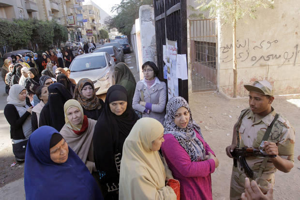 Egyptian women line up outside a polling station to cast their votes in the second round of a referendum on a disputed constitution drafted by Islamist supporters of President Mohammed Morsi in Giza, Egypt, Saturday, Dec. 22, 2012. (AP Photo/Amr Nabil)