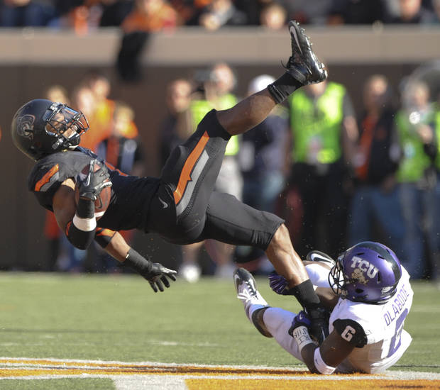 TCU safety Elisha Olabode, right, tackles Oklahoma State running back Joseph Randle, left, during the first half of an NCAA college football game in Stillwater, Okla., Saturday, Oct. 27, 2012. (AP Photo/Brody Schmidt)
