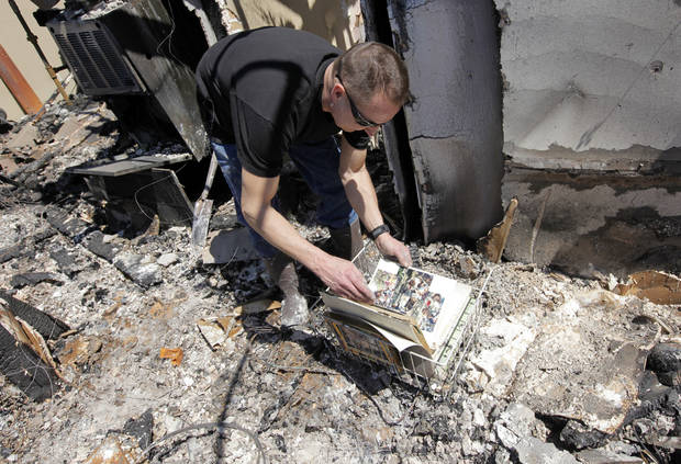 Todd Sewell looks through an album of pictures that managed to survive the fire which destroyed his home at 11533 Berkshire Ct. in Midwest City, Okla., Saturday, April 11, 2009. Wildfires struck the area on Thursday, April 9, 2009, destroying several homes. Photo by Nate Billings, The Oklahoman