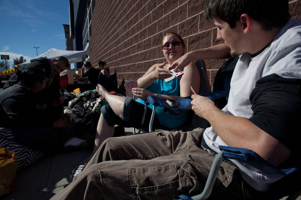 Matt Faulkner, right, and Victoria Tanski play a game of go fish while they wait in line Thursday, Nov. 22, 2012 for the Black Friday sale to begin at midnight at Best Buy in St. George, Utah. (AP Photo/The Spectrum & Daily News, Jud Burkett)