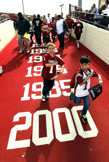 Fans run onto the field for autographs after the annual Spring Football Game at Gaylord Family-Oklahoma Memorial Stadium in Norman, Okla., on Saturday, April 13, 2013. Photo by Steve Sisney, The Oklahoman