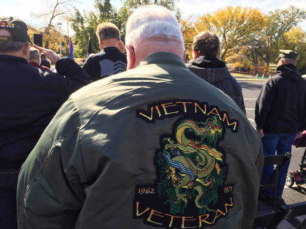 "Head bowed, Vietnam veteran Patrick Nelson stood for the playing of ""Taps"" on Thursday at a ceremony marking the arrival in Oklahoma City of The Wall That Heals, a replica of the Vietnam Veterans Memorial in Washington, D.C. The Wall is open to the public on the grounds of the Oklahoma History Center through 2 p.m. Sunday. [Photo by William Crum, The Oklahoman]"