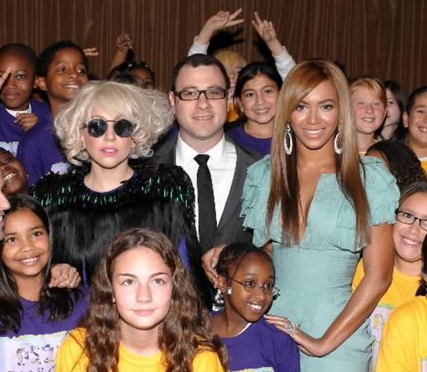 Lady Gaga and Beyonce pose with Billboard editor-in-chief  Bill Werde and a group of children at the Billboard Women in Music ceremony (AP photo by Evan Agostini)