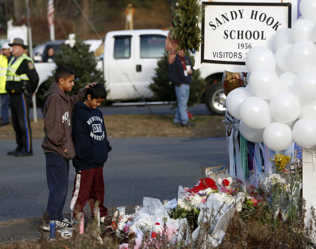 Brothers Thomas, 13, left, and Steven Leuci, 9, pay their respects at a memorial for shooting victims near Sandy Hook Elementary School, Saturday, Dec. 15, 2012 in Newtown, Conn.  A gunman walked into Sandy Hook Elementary School in Newtown Friday and opened fire, killing 26 people, including 20 children. (AP Photo/Jason DeCrow) ORG XMIT: CTJD114