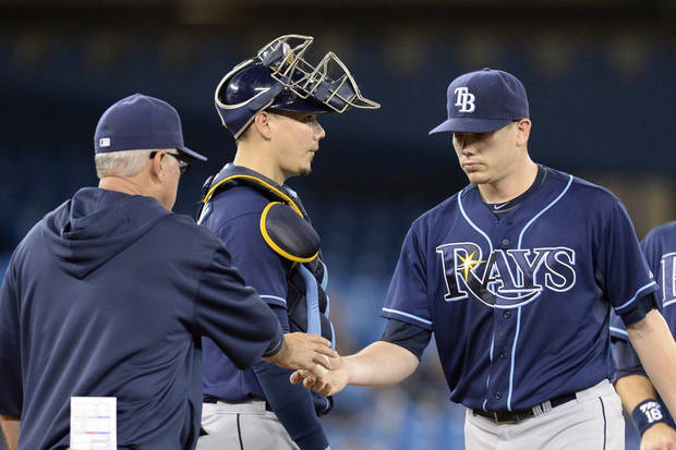 Tampa Bay Rays starter Jeremy Hellickson, right, is pulled from the game by manager Joe Maddon, left, as Rays' catcher Jose Lobaton, center, looks on during fifth-inning baseball game action against the Toronto Blue Jays in Toronto, Friday, Sept. 27, 2013. (AP Photo/The Canadian Press, Frank Gunn)