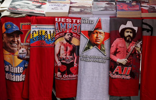 Iconic T-shirts styled with images of Venezuela&#039;s President Hugo Chavez are displayed for sale next to a T-shirt of Venezuelan musician Ali Primera, in Caracas, Venezuela, Friday, Dec. 28, 2012. The obsessive, circular conversations about Chavez&#039;s health dominate family dinners, plaza chit-chats and social media sites in this country on edge since its larger-than-life leader went to Cuba for emergency cancer surgery more than two weeks ago. The man whose booming voice once dominated the airwaves for hours at a time has not been seen or heard from since.(AP Photo/Fernando Llano)