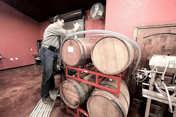 Thomas Ingmire pulls a sample from wine aging in barrels. Photo by STEVE GOOCH, THE OKLAHOMAN