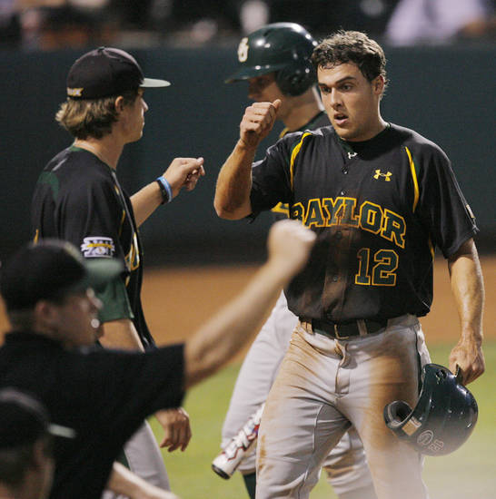 Baylor's Chris Slater (12) is greeted by teammates after scoring in the sixth inning during the Big 12 baseball championship tournament game between Baylor and Kansas at the Bricktown Ballpark in Oklahoma City, Saturday, May 29, 2010. Photo by Nate Billings, The Oklahoman