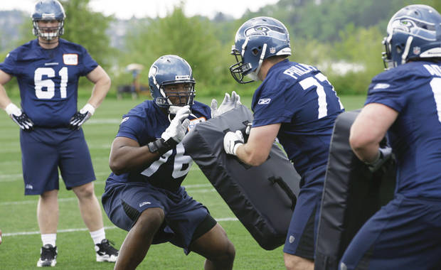 Former OSU standout Russell Okung, center left, squares off against rookie tackle Jacob Phillips, center right, as Mitch Erickson looks on at left during the Seahawks' rookie minicamp Friday in Renton, Wash. AP Photo