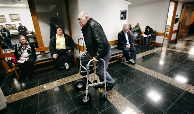 A man uses a walker as he passes others after his name was called to meet with an attorney Thursday at Workers� Compensation Court in the Denver Davison Building near the state Capitol in Oklahoma City. Photos by Jim Beckel, The Oklahoman