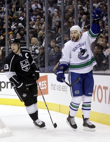 Vancouver Canucks right wing Zack Kassian, right, celebrates his goal as Los Angeles Kings right wing Dustin Brown looks away during the first period of an NHL Hockey game in Los Angeles, Monday, Jan. 28, 2013. (AP Photo/Chris Carlson)