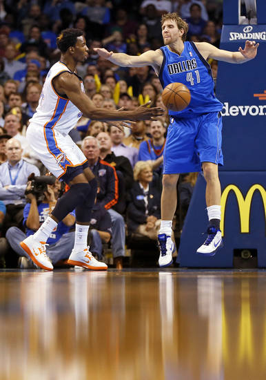 Oklahoma City's Hasheem Thabeet (34) passes around Dallas' Dirk Nowitzki (41) during an NBA basketball game between the Oklahoma City Thunder and the Dallas Mavericks at Chesapeake Energy Arena in Oklahoma City, Monday, Feb. 4, 2013. The Thunder won. 112-91. Photo by Nate Billings, The Oklahoman