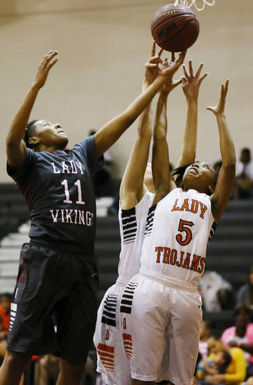 Northeast's Dani Gaddis (11) battles for a rebound against Tierra East (5) and Mia Truss (30) of Douglass during a girls high school basketball game between Douglass and Northeast at Douglass High School in Oklahoma City, Friday, Feb. 8, 2013. Photo by Nate Billings, The Oklahoman