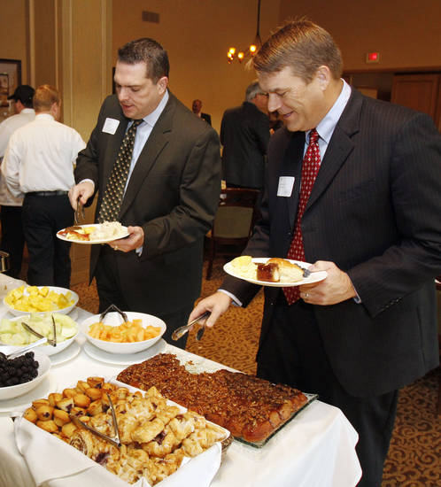 Sen. Clark Jolley, R-Edmond, left, and Rep. Lewis H. Moore, R-Arcadia, get breakfast before speaking to the Edmond Area Chamber of Commerce.