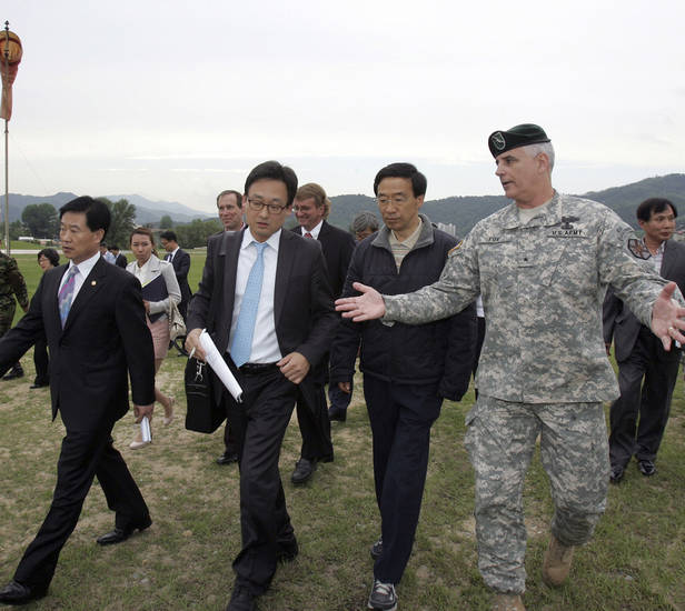 Left: South Korean fact-finding mission members are guided by U.S. Army Brig. Gen. David Fox, right, during their visit to Camp Carroll, in Chilgok, southeast of Seoul, on May 23. AP PHOTOS
