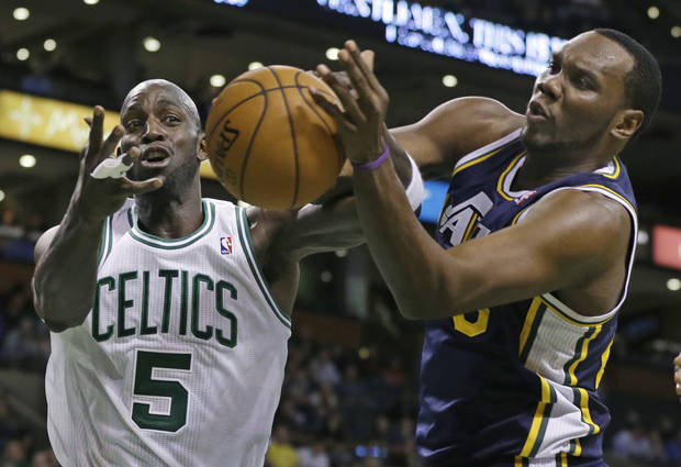 Boston Celtics power forward Kevin Garnett (5) battles for a loose ball with Utah Jazz center Al Jefferson (25) during the first half of an NBA basketball game in Boston, Wednesday, Nov. 14, 2012. (AP Photo/Elise Amendola)