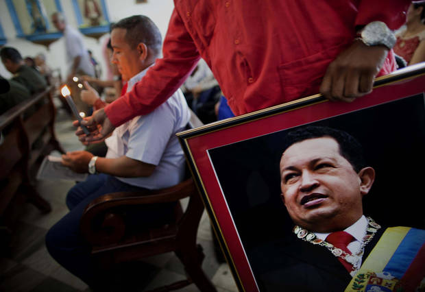"A Venezuelan embassy worker holds a framed image of Venezuela's ailing President Hugo Chavez during the monthly Catholic service devoted to the sick at the Church of Our Lady of Regla, in Regla, across the bay from Havana, Cuba, Tuesday, Jan. 8, 2013. Venezuela's government said Monday, Chavez is in a ""stable situation"" in a Cuban hospital receiving treatment due to a severe respiratory infection. The update came as other government officials reiterated their stance that the president need not be sworn in for a new term as scheduled this Thursday and could instead have his inauguration at a later date. (AP Photo/Ramon Espinosa)"