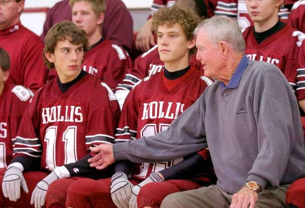 Hollis, Okla. - Nov. 7, 2003. Former Texas coach and Hollis high school football player Darrell K Royal, right, reaches over Dustin Adams, middle, to talk to Justin Fletcher, left, as the Hollis Tigers pose for a picture with Coach Royal at Hollis High School. Hollis has named their football field after Royal. Photo by Nate Billings, The Oklahoman