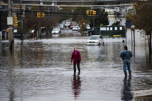 A woman stands in a street flooded by superstorm Sandy, Wednesday, Oct. 31, 2012, in the Staten Island borough of New York. Sandy, the storm that made landfall Monday, caused multiple fatalities, halted mass transit and cut power to more than 6 million homes and businesses. (AP Photo/John Minchillo) ORG XMIT: NYJM111