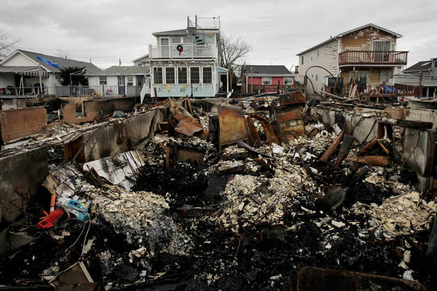 A Christmas wreath is displayed on the second floor porch railing of a home adjacent to the fire-damaged zone in the Breezy Point section of New York, Friday, Dec. 7, 2012. Over 100 homes were burned to the ground during Superstorm Sandy. (AP Photo/Mark Lennihan)