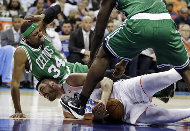 Charlotte Bobcats' Byron Mullens (22) holds onto the ball as Boston Celtics' Paul Pierce (34) falls on him during the first half of an NBA basketball game in Charlotte, N.C., Monday, Feb. 11, 2013. (AP Photo/Chuck Burton)