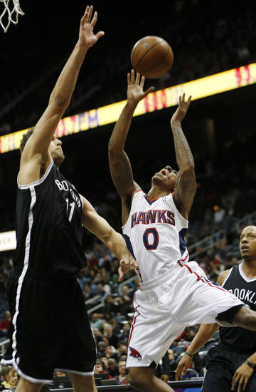 Atlanta Hawks point guard Jeff Teague (0) is defended by Brooklyn Nets center Brook Lopez (11) while going to the basket in the first half of an NBA basketball game on Wednesday, Jan. 16, 2013, in Atlanta. (AP Photo/John Bazemore)