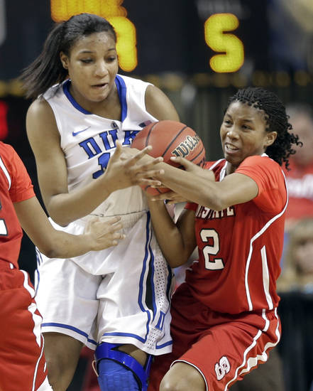 Duke's Richa Jackson, left, and North Carolina State's Len'Nique Brown, right, battle for control of a loose ball during the first half of an NCAA college basketball game at the Atlantic Coast Conference tournament in Greensboro, N.C., Friday, March 8, 2013. (AP Photo/Chuck Burton) ORG XMIT: NCCB114