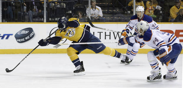 Nashville Predators right wing Chris Mueller, left, shoots and scores against the Edmonton Oilers as Ryan Smyth (94) and Corey Potter (44) give chase in the second period of an NHL hockey game on Monday, March 25, 2013, in Nashville, Tenn. (AP Photo/Mark Humphrey)