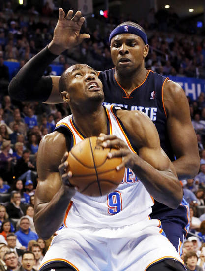Oklahoma City's Serge Ibaka (9) tries to get the ball past Charlotte's Brendan Haywood (33) during an NBA basketball game between the Oklahoma City Thunder and Charlotte Bobcats at Chesapeake Energy Arena in Oklahoma City, Monday, Nov. 26, 2012.  Photo by Nate Billings , The Oklahoman