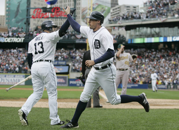   Detroit Tigers&#039; pinch runner Don Kelly, right, is met at the dugout by teammate Alex Avila after scoring on a wild pitch by Oakland Athletics relief pitcher Ryan Cook during the eighth inning of Game 2 of the American League division baseball series, Sunday, Oct. 7, 2012, in Detroit. (AP Photo/Duane Burleson)  
