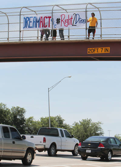 Amir Darvishzadeh hold a sign while protesting on the walk bridge over Interstate 44 in Woodson Park. The rally was a part of a national effort to raise awarness about the Dream Act. <strong>David McDaniel - The Oklahoman</strong>