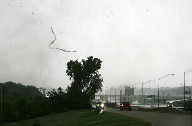 Debris flies across an I-35 access road as a tornado moves through Edmond, Okla., Sunday, May 19, 2013. Photo by Dave Fisk, for The Oklahoman