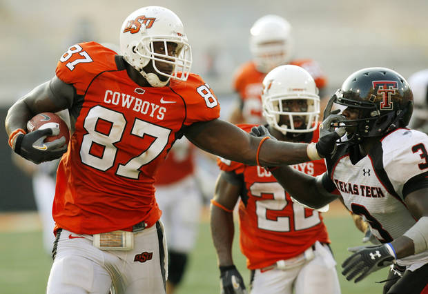 OSU's Brandon Pettigrew (87) stiff arms Jamar Wall (3) Texas Tech on his way to a touchdown in the fourth quarter of the college football game between the Oklahoma State University Cowboys (OSU) and the Texas Tech University Red Raiders (TTU) at Boone Pickens Stadium in Stillwater, Okla., on Saturday, Sept. 22, 2007. OSU won, 49-45. By NATE BILLINGS, The Oklahoman