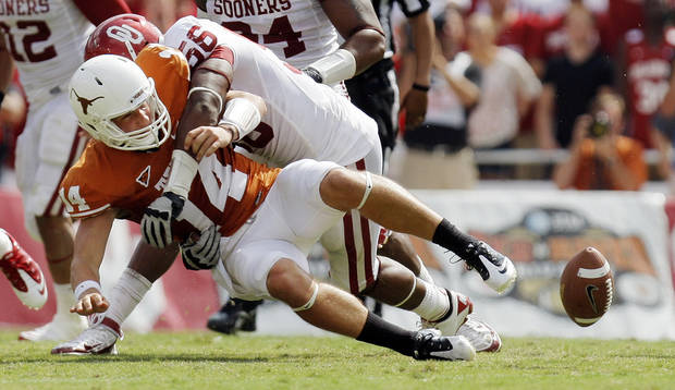 UT's David Ash (14) fumbles the ball as he is brought down by Ronnell Lewis (56) of OU in the second half during the Red River Rivalry college football game between the University of Oklahoma Sooners (OU) and the University of Texas Longhorns (UT) at the Cotton Bowl in Dallas, Saturday, Oct. 8, 2011. OU won, 55-17. Photo by Nate Billings, The Oklahoman