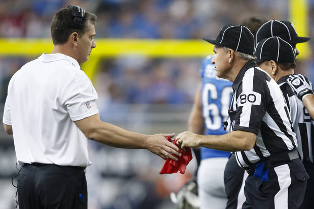Field judge Greg Gautreaux (80) hands the red challenge flag back to Detroit Lions head coach Jim Schwartz in the first half of an NFL football game against the Houston Texans at Ford Field in Detroit, Thursday, Nov. 22, 2012. Houston won 34-31 in overtime. (AP Photo/Rick Osentoski)