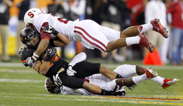 Oklahoma State's Colton Chelf (83) is brought down by Michael Thomas (3) and Delano Howell (26) during the Fiesta Bowl between the Oklahoma State University Cowboys (OSU) and the Stanford Cardinal at the University of Phoenix Stadium in Glendale, Ariz., Monday, Jan. 2, 2012. Photo by Bryan Terry, The Oklahoman