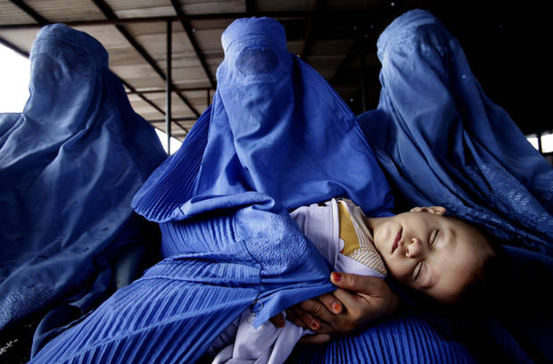 FILE - In this Thursday, April 22, 2010 photo, Afghan refugee women wait for transport to leave for Afghanistan at a repatriation center run by the United Nations High Commissioner for Refugees, in Peshawar. Pakistan has extended refugee status for over a million Afghans in the country by an additional six months, the government announced a move likely to ease fears of Afghans living in Pakistan that they would soon have to return home. (AP Photo/Mohammad Sajjad, File)