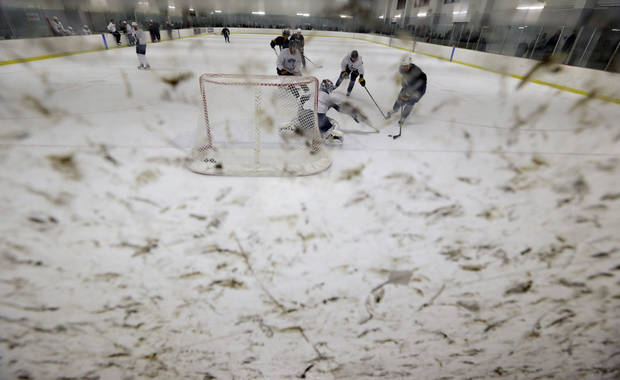 As shown through the puck stained safety glass, Buffalo Sabres goalie Ryan Miller makes a save on a shot by Sabres' Alexander Sulzer (52) during an informal NHL hockey workout in Amherst, N.Y., Friday, Jan. 11, 2013. (AP Photo/David Duprey)