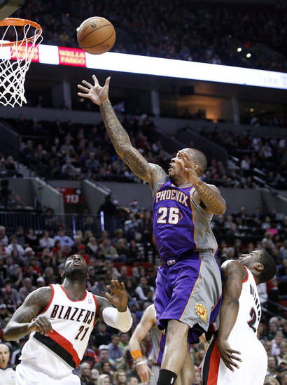 Phoenix Suns guard Shannon Brown (26) shoots between Portland Trail Blazers guard Wesley Matthews, right, and center J.J. Hickson during the first quarter of an NBA basketball game in Portland, Ore., Saturday, Dec. 22, 2012. (AP Photo/Don Ryan)