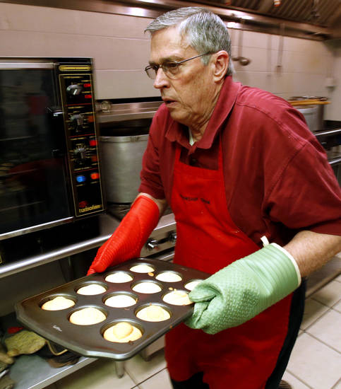 E.H. Eley pulls some hot cornbread from the oven Tuesday at the annual Benefit Bean Dinner sponsored by the Christian Men's Fellowship at First Christian Church. The dinner raises money for Health for Friend's medication fund. PHOTO BY STEVE SISNEY, THE OKLAHOMAN <strong>STEVE SISNEY</strong>