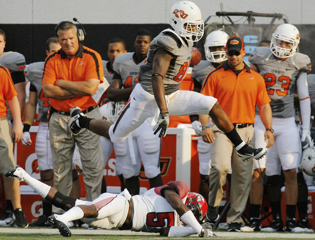 "OSU's Tracy Moore leaps over Dwight ""Bill"" Bentley of La.Lafayette during the first quarter of their game in Stillwater on Saturday. Photo by Nate Billings, The Oklahoman"