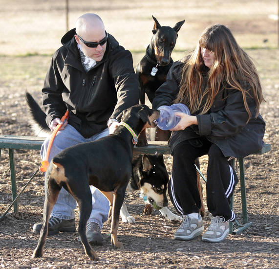 Austin and Donna Little take advantage of sunny weather Wednesday and exercise their dogs, Iblis and Shady, at the dog park in northeast Norman. PHOTO BY STEVE SISNEY, THE OKLAHOMAN