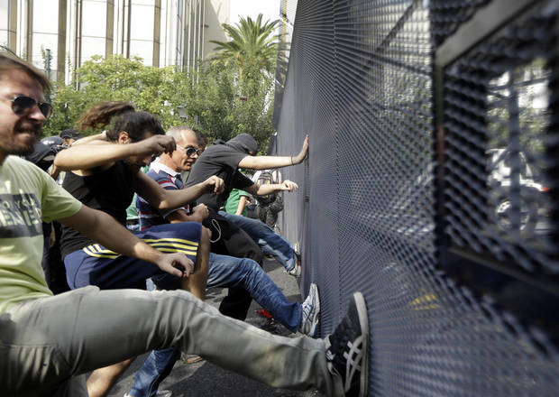 FILE - This Oct. 9, 2012 file photo shows protesters kicking a police barrier during a protest in front of the parliament in Athens. Europe is struggling to control a debt crisis, save the euro currency and stop a repeat of the 2008 financial crisis that sent the world spinning into recession. The continent�s troubles are the No. 1 threat to the fragile U.S. economy. If the crisis spreads to the U.S., Americans could find it harder to get loans and the country could slip back into recession. (AP Photo/Lefteris Pitarakis, File)