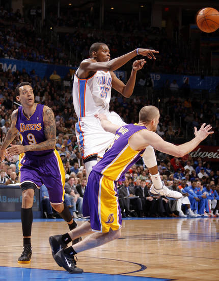Oklahoma City's Kevin Durant (35) passes the ball from between Los Angeles' Matt Barnes (9) and Steve Blake (5) during an NBA basketball game between the Oklahoma City Thunder and the Los Angeles Lakers at Chesapeake Energy Arena in Oklahoma City, Thursday, Feb. 23, 2012. Photo by Bryan Terry, The Oklahoman