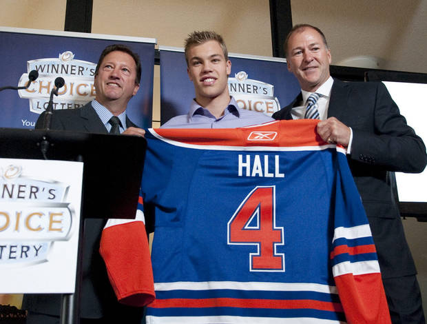 Edmonton Oilers general manager Steve Tambellini, left, holds up a jersey with draft pick Taylor Hall, center, and Kevin Lowe, the NHL team's president of hockey operations, in Edmonton, Alberta, on Wednesday, Sept. 8, 2010. Lowe, the Oilers' first-ever draft pick and only player to wear the number since Edmonton entered the NHL in 1979, passed his No. 4 to Hall, the centerpiece of a full-scale rebuild in Edmonton and the franchise's first No. 1 overall draft pick. (AP Photo/The Canadian Press, John Ulan) ORG XMIT: JCU102