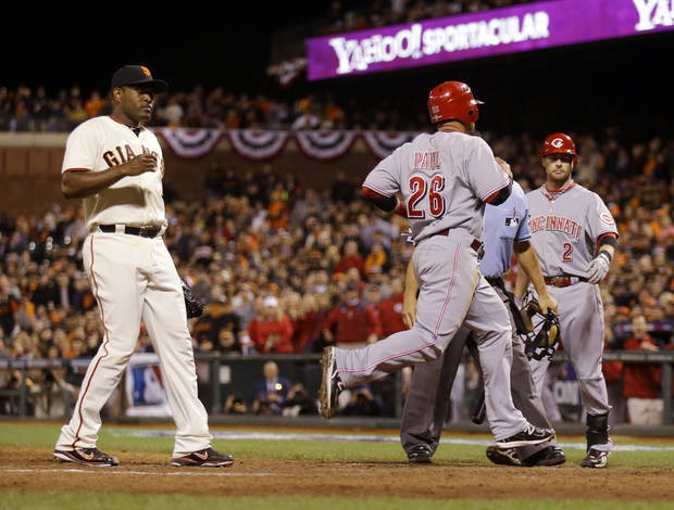 Cincinnati Reds left fielder Xavier Paul (26) scores on a wild pitch by San Francisco Giants pitcher Santiago Casilla, left, in the ninth inning of Game 1 of the National League division baseball series in San Francisco, Saturday, Oct. 6, 2012. (AP Photo/Marcio Jose Sanchez)