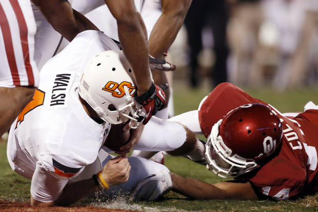 Oklahoma State's J.W. Walsh (4) scores as Oklahoma's Aaron Colvin (14) reaches for him during the second half of the Bedlam college football game in which  the University of Oklahoma Sooners (OU) defeated the Oklahoma State University Cowboys (OSU) 51-48 in overtime at Gaylord Family-Oklahoma Memorial Stadium in Norman, Okla., Saturday, Nov. 24, 2012. Photo by Steve Sisney, The Oklahoman