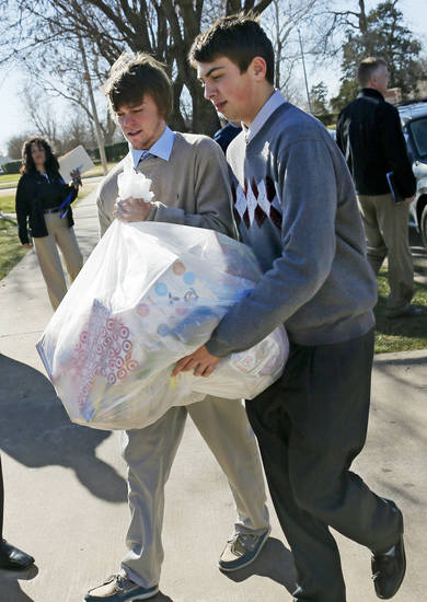 Mount St. Mary basketball players Cam Adney, right, and Mak Corder carry donated items Friday at Sacred Heart Catholic Church, 2706 S Shartel, in Oklahoma City. Players from the teams participating in Hoops 4 Hope loaded items they donated to Catholic Charities into a truck after having Mass to start the event. Photo by Nate Billings, The Oklahoman <strong>NATE BILLINGS</strong>
