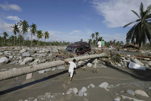 Residents search for victims of Tuesday's flash flood caused by Typhoon Bopha at New Bataan township, Compostela Valley in southern Philippines Thursday Dec. 6, 2012. The powerful typhoon that washed away emergency shelters, a military camp and possibly entire families in the southern Philippines has killed hundreds of people with nearly 400 missing, authorities said Thursday. (AP Photo/Bullit Marquez)